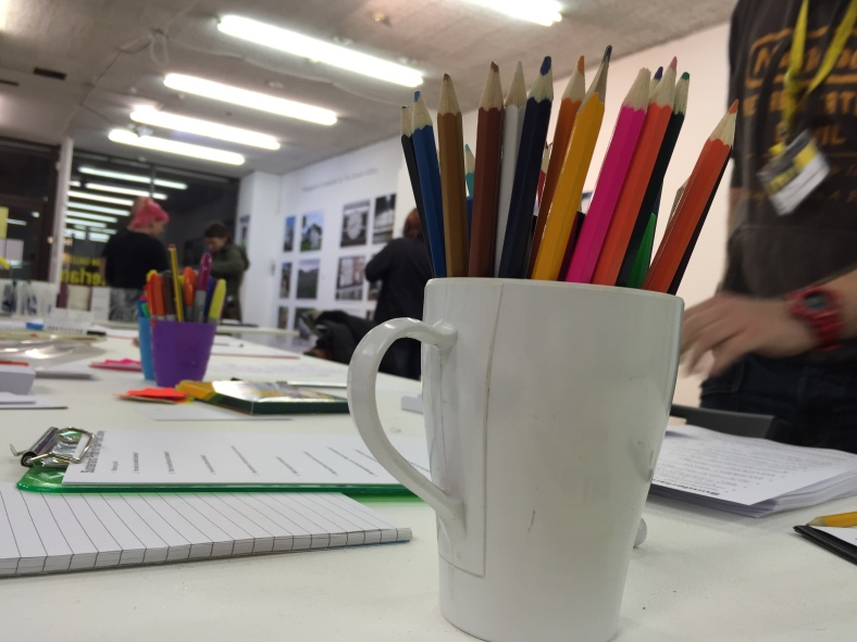 Some coloured pencils and surveys on the table at the Caravan Gallery's open event. In the background, some people are chatting and looking at the photography on display