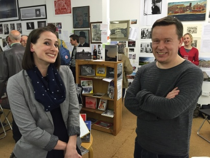 Two attendees to the Caravan Gallery's event . Behind; a small crowd of people, a bookshelf containing several books with their fronts on display, and a wall of photographs and artwork.